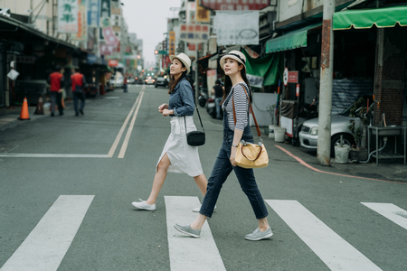 Photo pour two happy female friends travelers with bags crossing street together outdoor sunny day in china town. - image libre de droit
