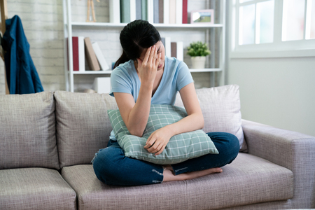 Photo pour stress headache health care and people concept. unhappy asian woman housewife with closed eyes headache sitting on couch against window in cozy living room at home. - image libre de droit