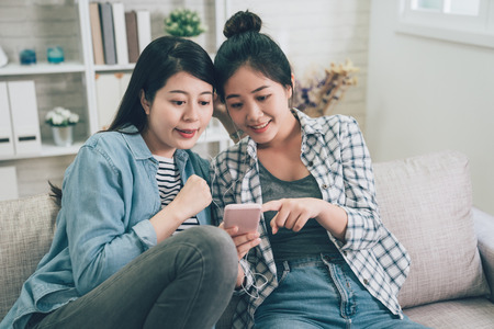 Photo pour Front view portrait of two joyful asian female friends listening music in living room at home. - image libre de droit