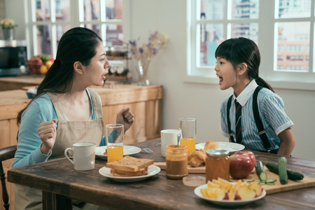 Foto de Beautiful asian woman housewife with bad little girl daughter screaming at each other. Concept of family conflict. angry mom and kid in uniform argue in breakfast time in morning before school. - Imagen libre de derechos