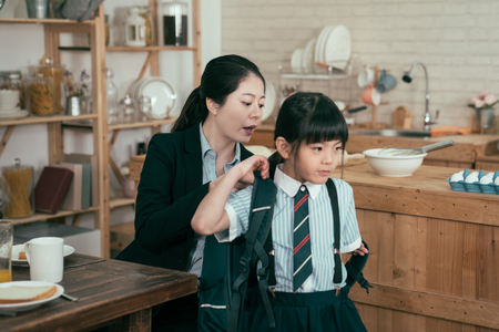 Foto de young mother worker in business suit help daughter get ready for school. Mom support child to wear backpack bag in wooden kitchen talking nag to little girl after breakfast time leaving home to study - Imagen libre de derechos