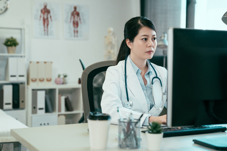 Photo for asian female doctor working with personal computer and writing on paperwork. Hospital background. chinese woman medical staff wear white robe in clinic office typing online patient document internet. - Royalty Free Image