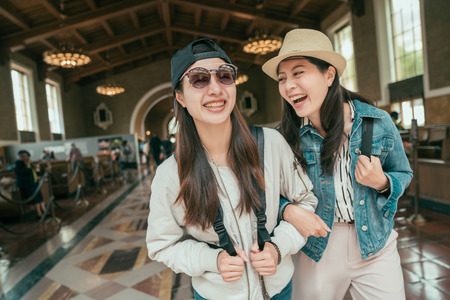 Foto de Two beautiful asian girls commute walking in railway train union station talking and laughing. Lifestyle tourism and friendship concepts. young happy women travelers arms in arms historical building - Imagen libre de derechos