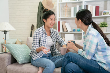 Photo pour Happy asian japanese female friends at home sitting on couch. two young women with coffee chatting on sofa gossiping and sharing secrets discussing life and relations. Friendship trust concept - image libre de droit