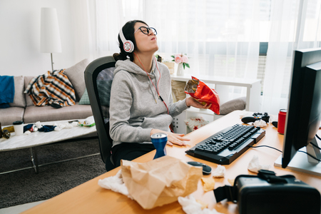 Foto de lazy college girl in messy dirty bedroom with order in junk food snack enjoy unhealthy life on summer break. happy young asian weird woman with headphones and glasses laughing binge watching online - Imagen libre de derechos
