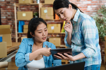 group of young Asian people working on small business startup at home office. online marketing shopping and packaging delivery. female freelance teamwork discussing on digital tablet concept indoors