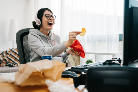 Foto de happy asian female nerd holding bag of chip snack junk food with trash on desk looking monitor laughing. relax lazy teenage girl at home watch comedy movie on computer with headset sit in messy room - Imagen libre de derechos