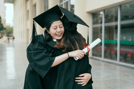 Photo pour Happy asian female graduate with classmate celebrating graduation. young girls best friends hugging each other close eyes love care bye cannot bear to separate. friendship authentic lifestyle concept - image libre de droit