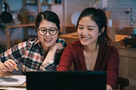 Foto de girl in eyeglasses laughing together with cheerful asian female student during common work at modern laptop computer in home kitchen using wireless internet at night. happy women looking at screen - Imagen libre de derechos