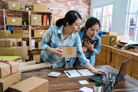 Photo pour beautiful pretty female employees using laptop computer working in warehouse and browsing online shopping order document to confirm stock goods. young girls holding parcel cardboard checking notebook - image libre de droit