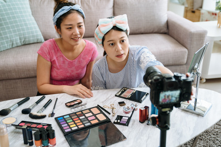 Photo pour two beauty blogger ready for recording make up tutorial video with cosmetic products on table in living room. - image libre de droit