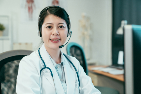 Photo pour female doctor wearing headset while using computer at desk in clinic office. - image libre de droit