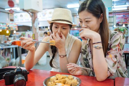 Foto de two young foreigner female travelers trying stinky tofu with chopsticks in local market. - Imagen libre de derechos
