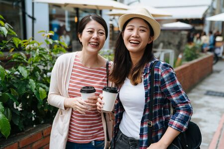 Outdoors fashion portrait of two cheerful asian girls friends drinking coffee walking in city.