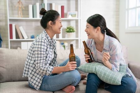Photo pour Two beautiful young asian female friends laughing in living room at home. - image libre de droit