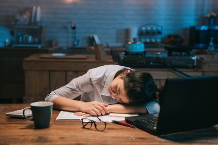 Foto de Sleepy exhausted asian woman employee working at wooden kitchen desk with laptop. - Imagen libre de derechos