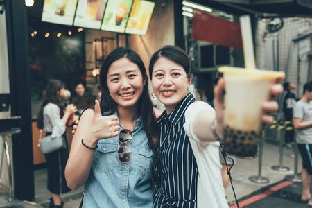 Foto de two pretty asian women tourist travel in taiwan taipei holding modern asian beverage bubble milk tea. girls showing face camera with tasty drink local specialty smiling with thumb up good on street - Imagen libre de derechos