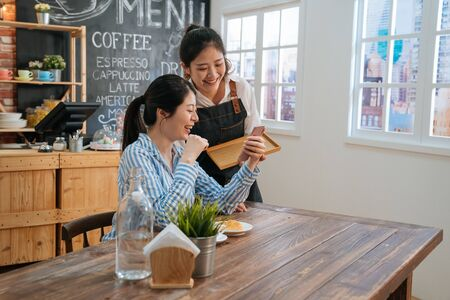 Photo pour two female friends in coffee shop chatting and discussing on social media with mobile phone. waitress in apron served lady regular customer and gossip with her looking together on smartphone screen. - image libre de droit