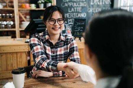 Photo for Smiling female candidate shaking hand with lady hr human resource manager in cafe bar. young girl joyful join new company got chance to work in dream office. success applicant job seeker coffee shop - Royalty Free Image