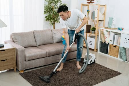 Photo pour Young asian japanese man cleaning carpet with vacuum cleaner at home living room. handsome guy doing housework in bright modern apartment. male household hardworking prepare tidy up for new year. - image libre de droit