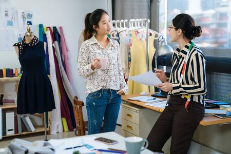Photo pour startup education fashion and studio concept. two asian smiling female designers having coffee break in office. group of creative team relax in workshop while discussing on sketch and drinking tea. - image libre de droit