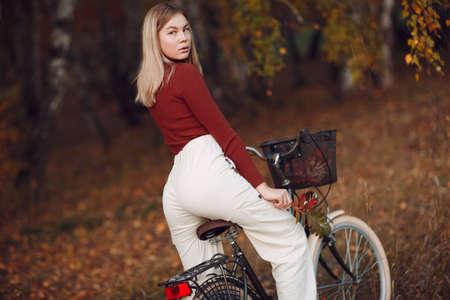 Foto für Happy active young woman riding bicycle in autumn park - Lizenzfreies Bild