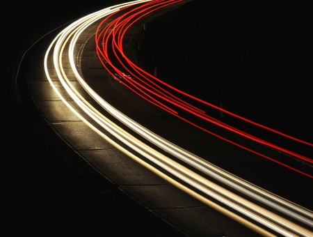 Fast cars are leaving light trails on night road