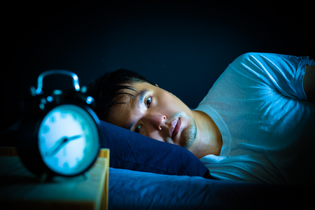 Photo pour asian man in bed suffering insomnia and sleep disorder thinking about his problem at night - image libre de droit