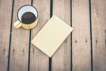 Photo pour Top view of a book and a cup of coffe on a wooden floor. Free time, relax, education and leisure concept. Still life everyday object on the table. Hot beverage in a mug and a blast. Warm yellow filter. - image libre de droit