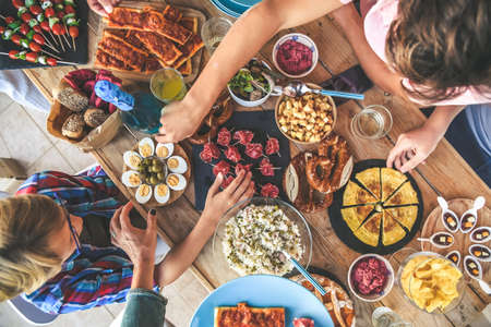 Photo pour Evening with friend dinner on the terrace enjoying together. Summer aperitif with group of friends Joy and festivities in family View from the top of a table with many foods Happy hands taking viands - image libre de droit