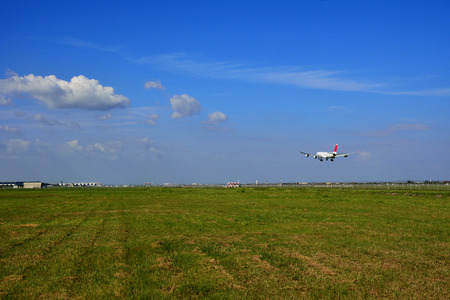 White airplane landing at airport with green grass field in foreground and blue sky and cloud in background