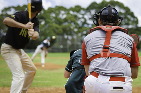 Baseball pitcher throwing ball to batter watched by Umpire and Catcher.の写真素材