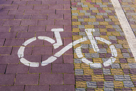 Bicycle route sign on the pavement in sunlight in a park. The ecological mode.