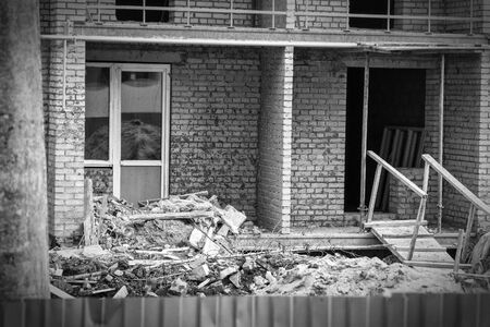 Photo for Construction debris next to a red brick house under construction. Garbage on the construction site. Black and white photo - Royalty Free Image