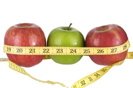 Row of green and red apples with a measuring tape around it.