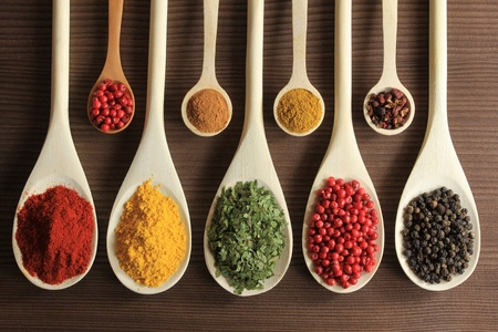 Colorful spices in wooden spoons - beautiful kitchen image.