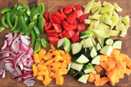 Colored peppers and onions diced on a chopping board