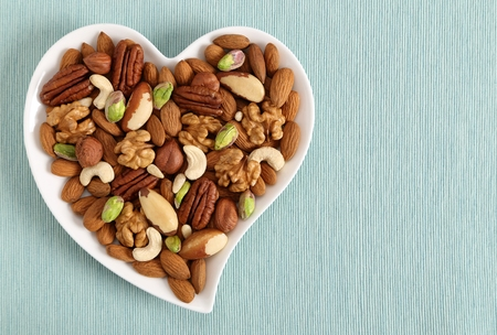 Photo pour Different types of nuts on a plate in the shape of a heart. Top view. - image libre de droit