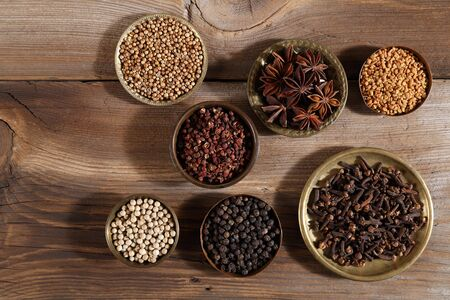 Photo for Brown aromatic spices in metal bowls on a wooden background. Top view. - Royalty Free Image