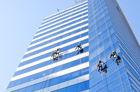 Group of workers cleaning windows of a tall building at Santiago de Chile