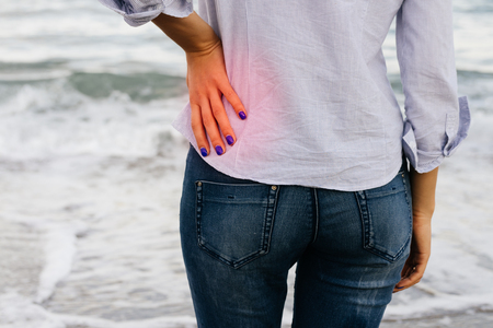 Low Back Pain. The woman in jeans and shirt standing on the shore and holding her lower back.