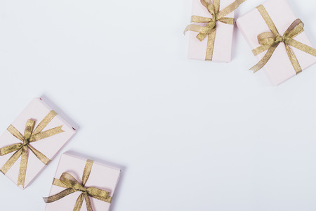 Pink gift boxes with golden ribbons and bows on white background, top view. Minimal flat lay frame with empty space in center of packed and prepared presents for the holiday.