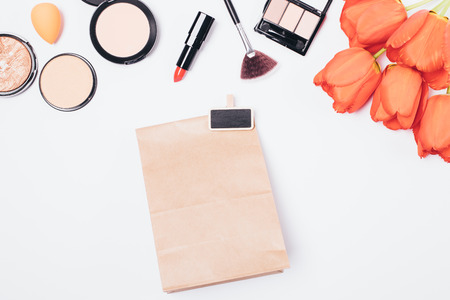 Photo pour Flat lay makeup background of women's lipsticks, brushes and powders with bouquet of flowers next to gift brown paper bag, top view on white table. - image libre de droit