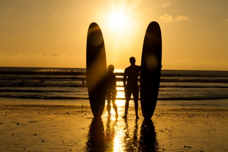 Surfer couple in silhouette holding long surf boards at sunset on tropical beach