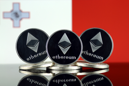 Physical version of Ethereum (ETH) and Malta Flag. Conceptual image for investors in cryptocurrency, Blockchain Technology, Smart Contracts, Personal Tokens and Initial Coin Offering.