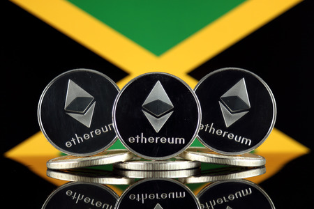 Physical version of Ethereum (ETH) and Jamaica Flag. Conceptual image for investors in cryptocurrency, Blockchain Technology, Smart Contracts, Personal Tokens and Initial Coin Offering.