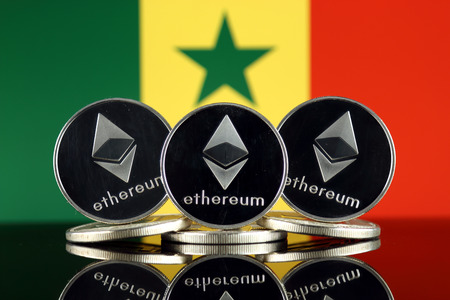 Physical version of Ethereum (ETH) and Senegal Flag. Conceptual image for investors in cryptocurrency, Blockchain Technology, Smart Contracts, Personal Tokens and Initial Coin Offering.