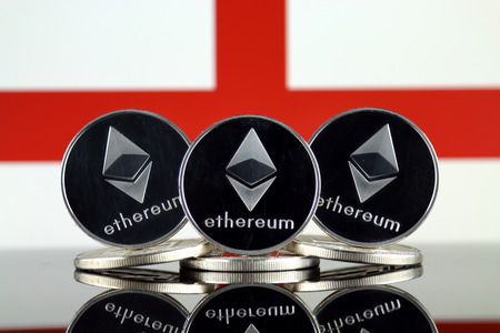 Physical version of Ethereum (ETH) and England Flag. Conceptual image for investors in cryptocurrency, Blockchain Technology, Smart Contracts, Personal Tokens and Initial Coin Offering.
