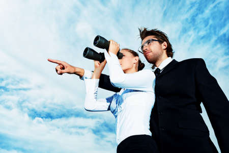 Photo pour Successful business people  standing over blue sky and purposefully looking away. - image libre de droit