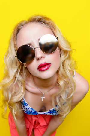 Photo for Attractive young woman wearing bright clothes and sunglasses over yellow background. Bright style, fashion. Optics style. - Royalty Free Image